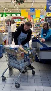 Ministr Marián Jurečka pomáhal v typické zástěře dobrovolníkům vykládat nakoupené zboží. Foto: Bps