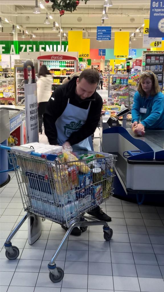 Pomáhal v typické zástěře dobrovolníkům vykládat nakoupené zboží.